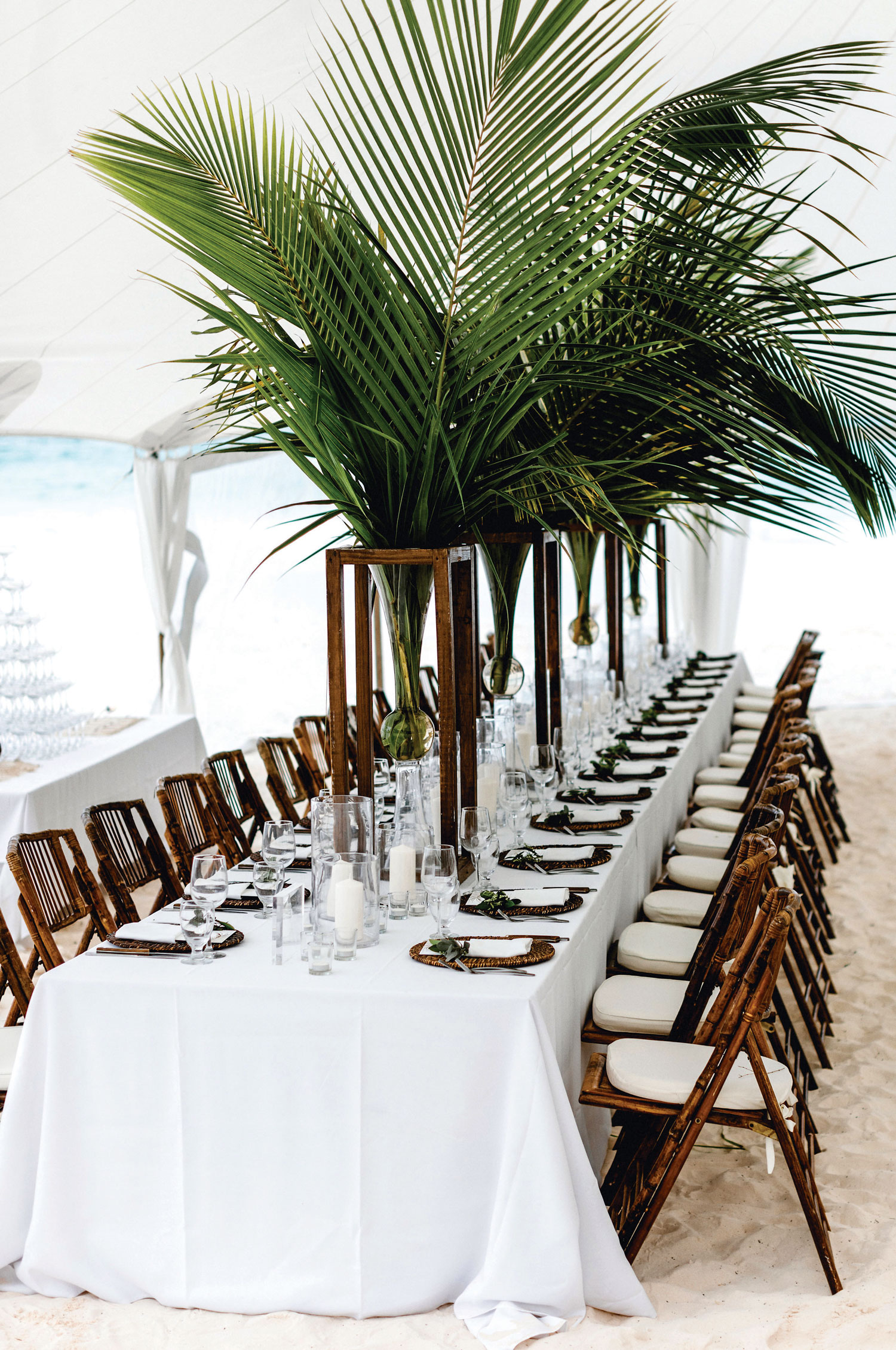 Inside Weddings magazine Spring 2019 issue destination wedding reception in the sand tall palm centerpiece
