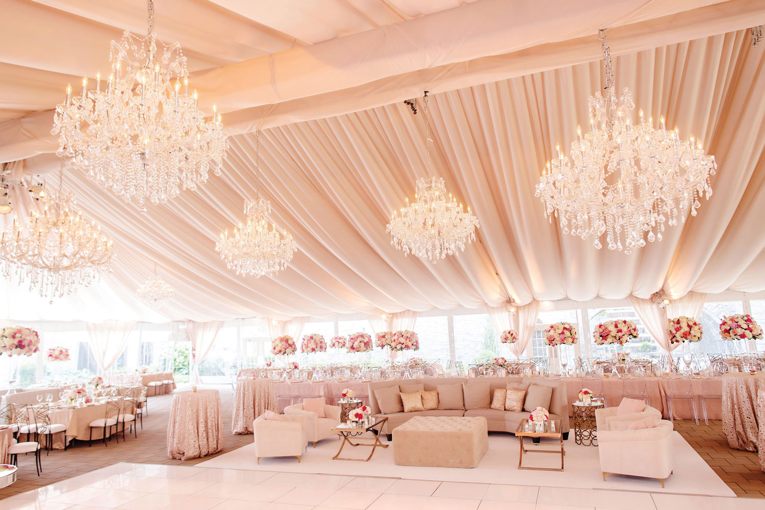 Inside Weddings Spring 2019 issue pretty wedding reception pink with drapery and chandeliers