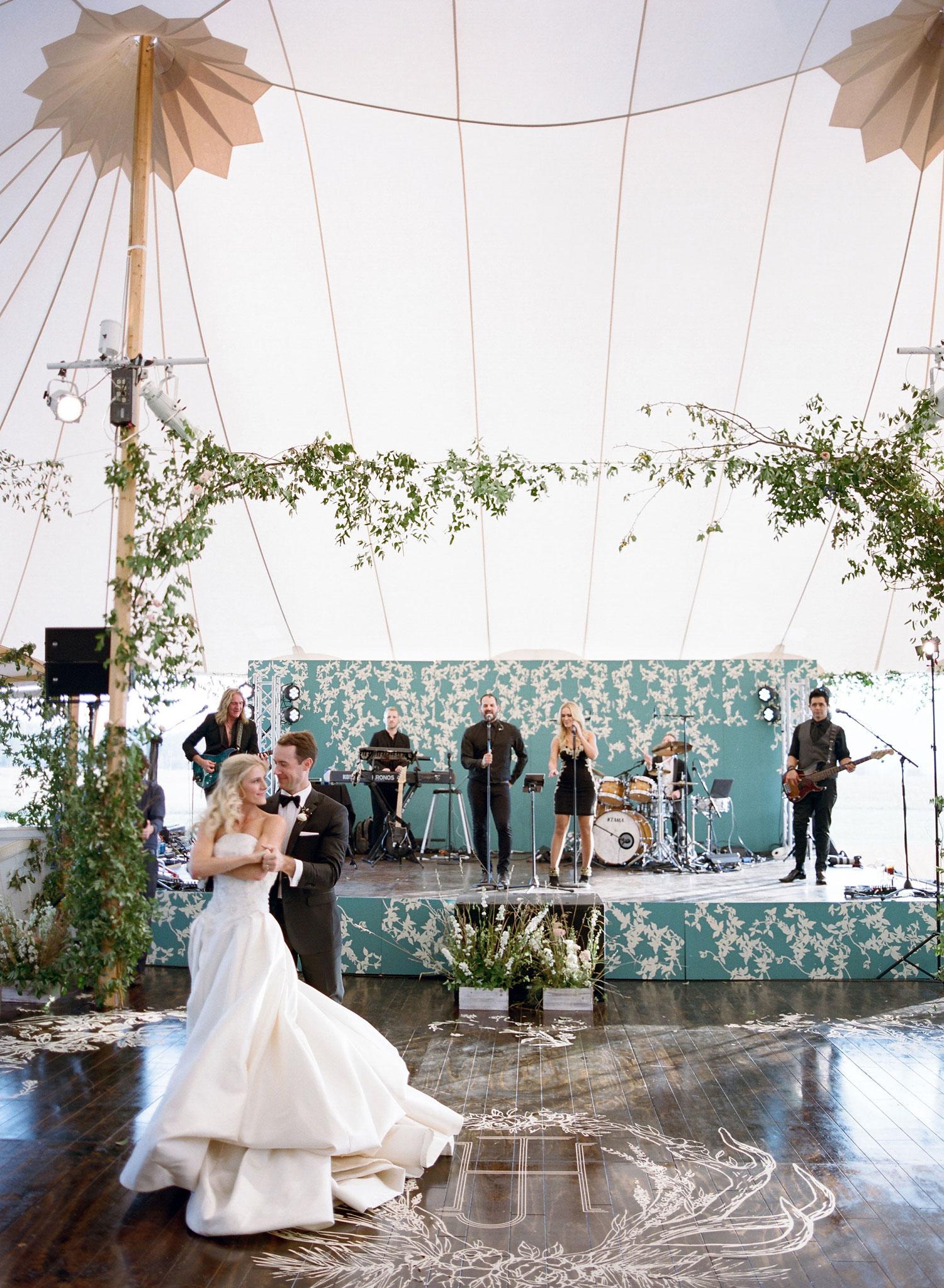 Bride and groom first dance on custom dance floor monogram stage backdrop emily clarke events