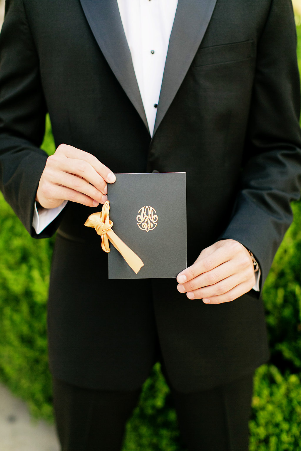 Groom holding black and gold wedding ceremony program booklet gold ribbon monogram