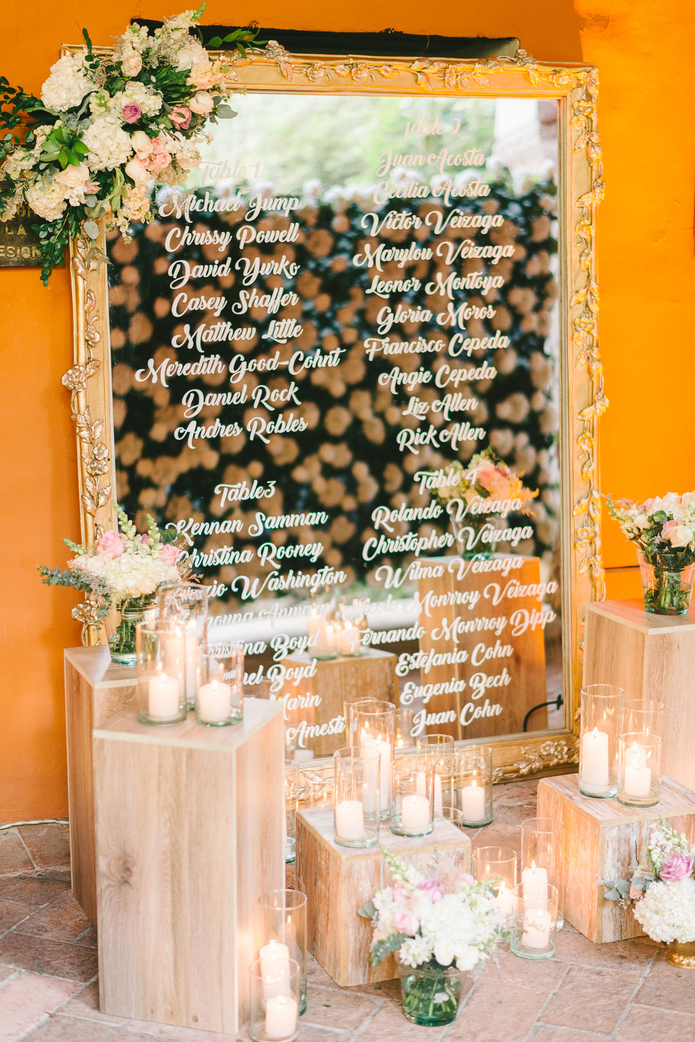 Large gold mirror seating chart with candles and neutral flowers white lettering calligraphy