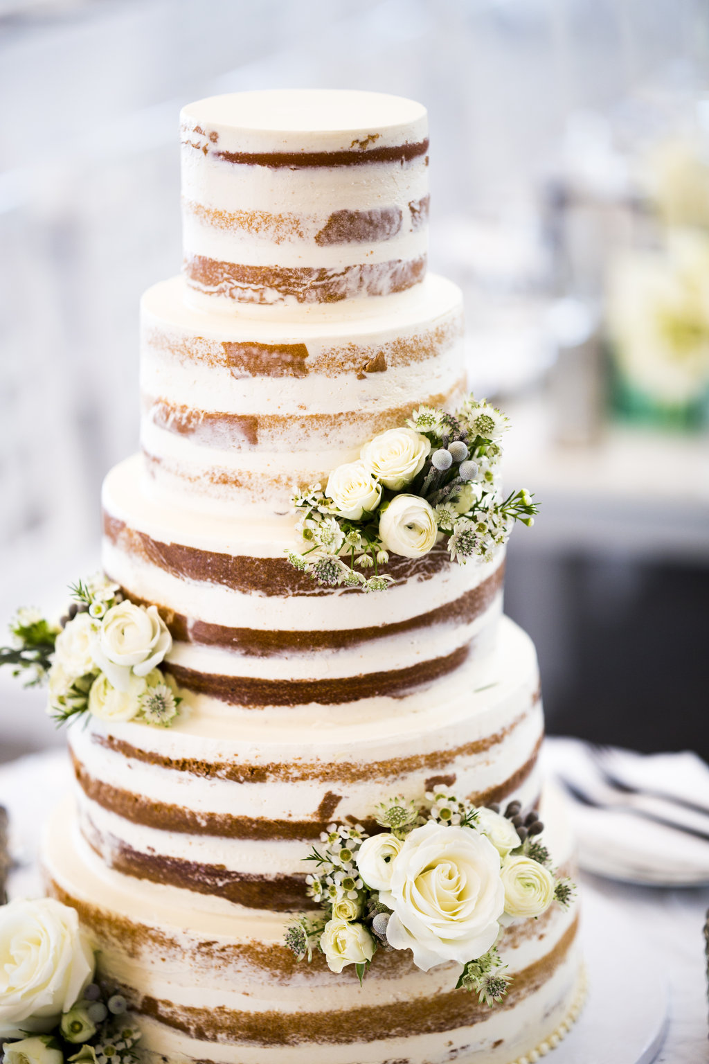 naked wedding cake with fresh ivory white flowers and greenery