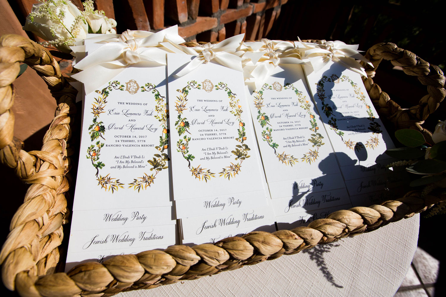 colorful wedding ceremony programs with bows in basket at outdoor wedding