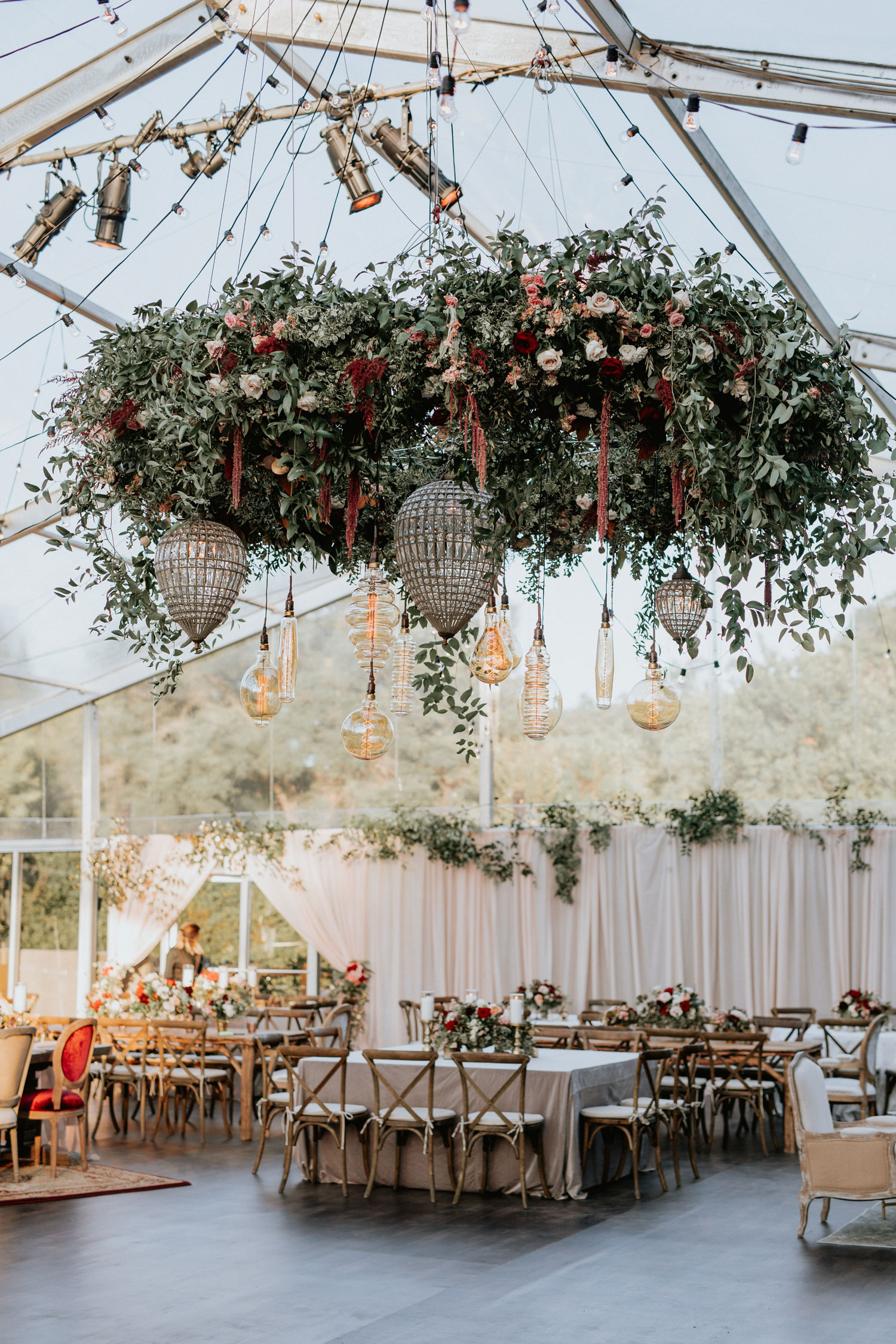 Clear tent wedding reception fall decor hues color palette ceiling installation flower chandelier