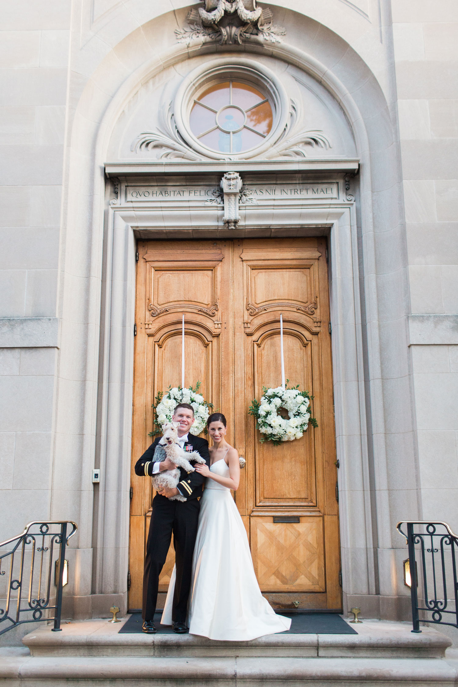 cute photo of bride and groom in front of wedding ceremony venue with dog holding puppy