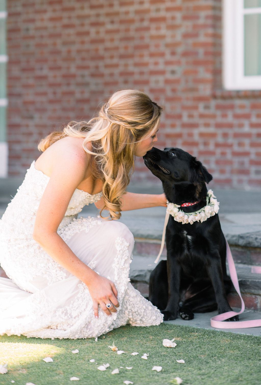 bride giving dog kiss before wedding portraits with puppy