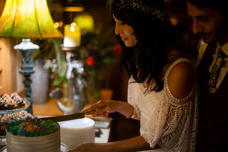 bride cutting one layer wedding cake at dessert table vegan wedding