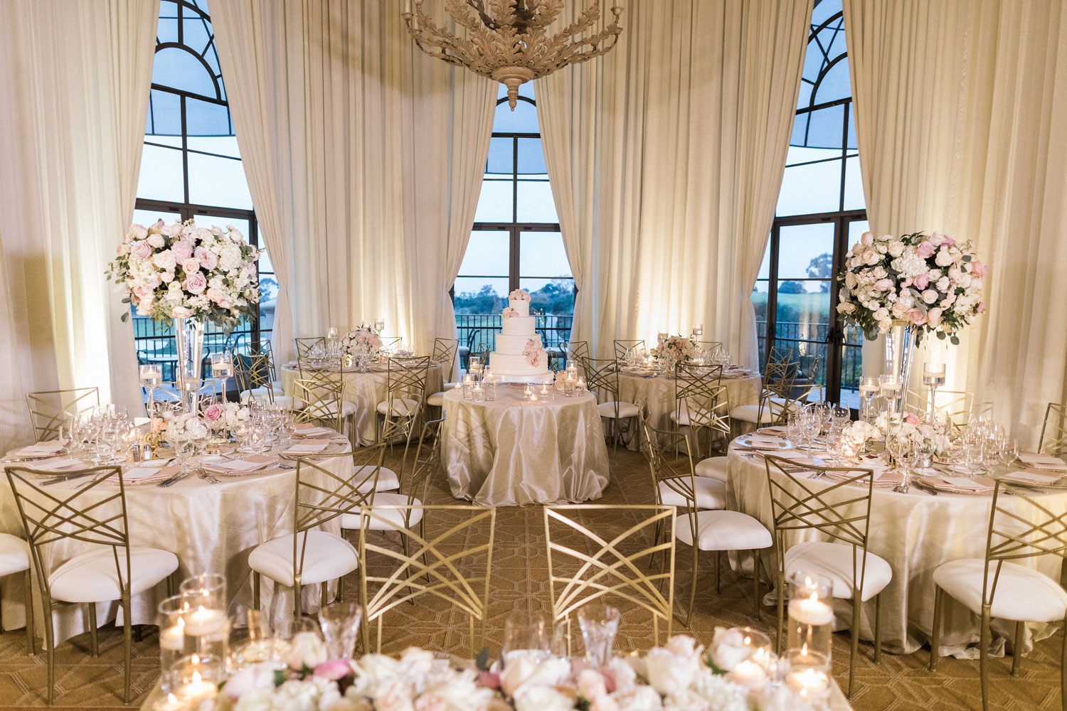 ballroom wedding ceremony with white and gold reception chairs chameleon chair collection