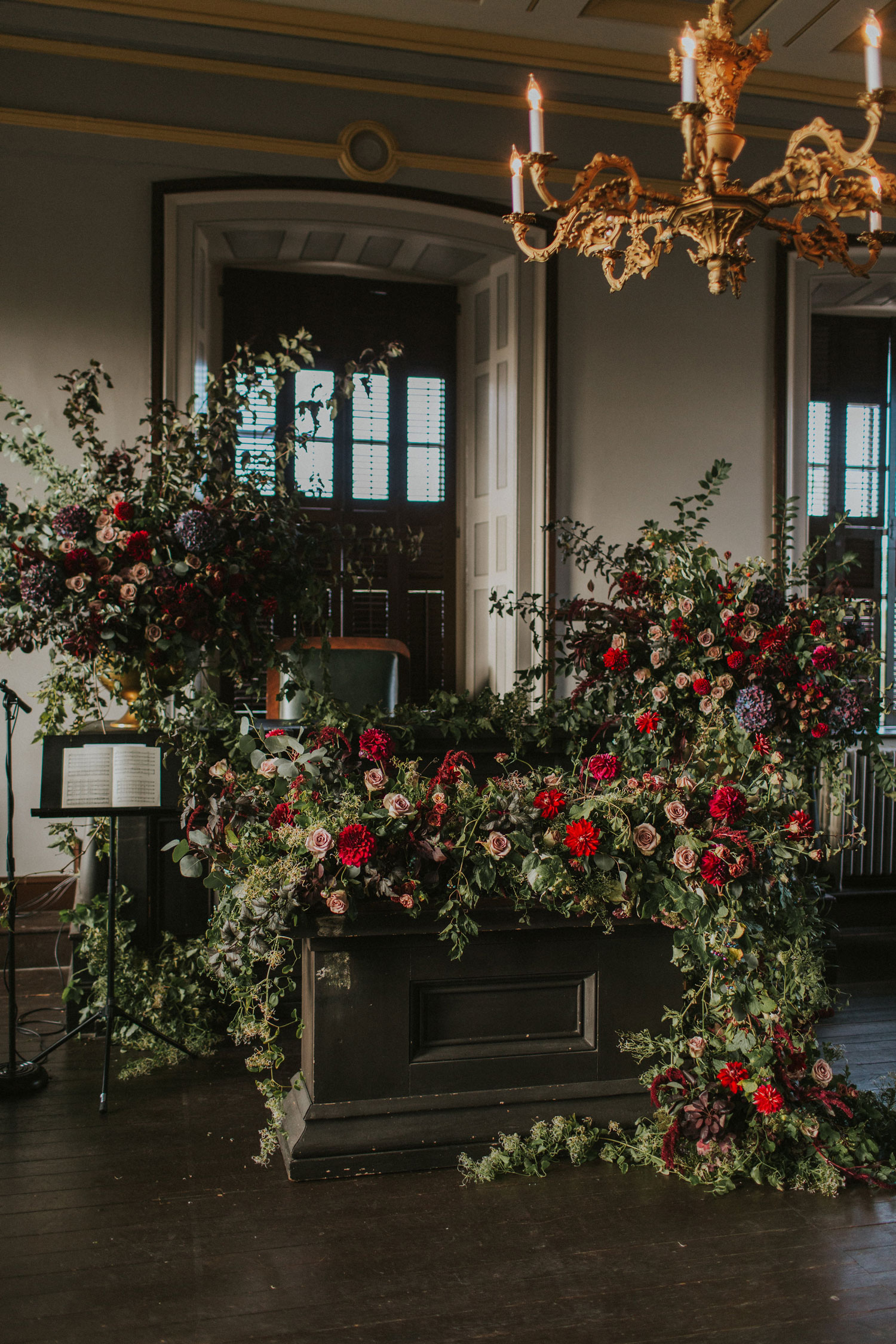 wedding ceremony with dark and moody color palette soft sunlight streaming in