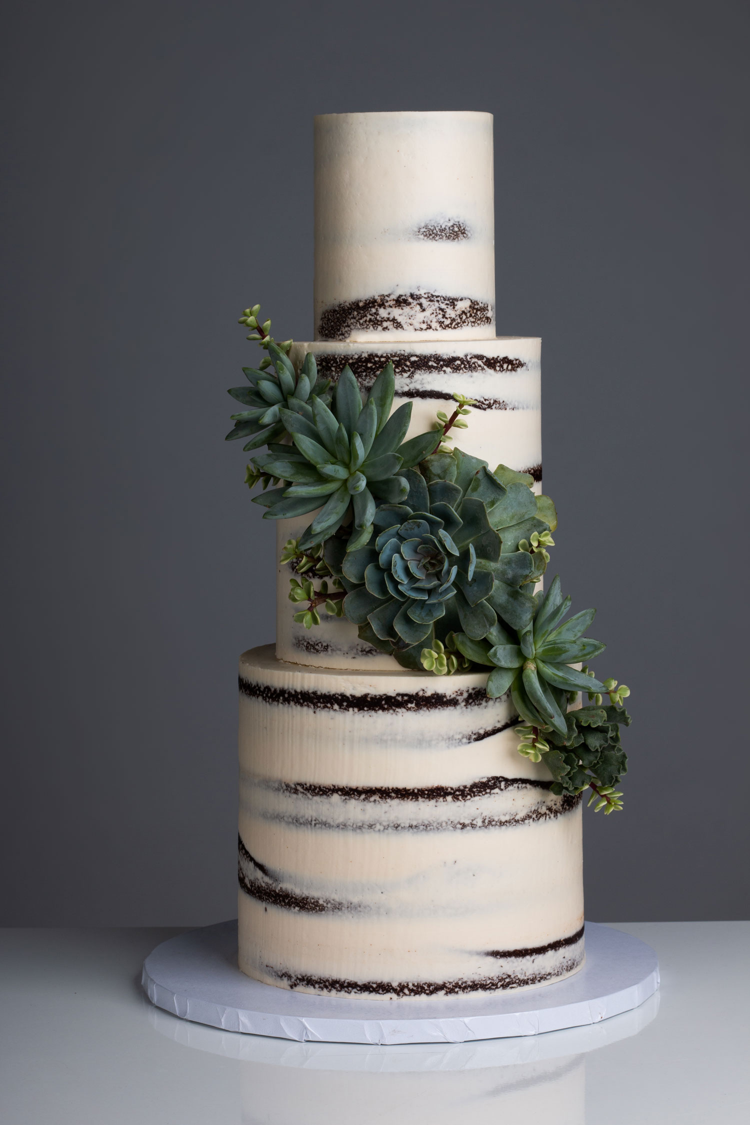 naked wedding cake with cascading succulent designs