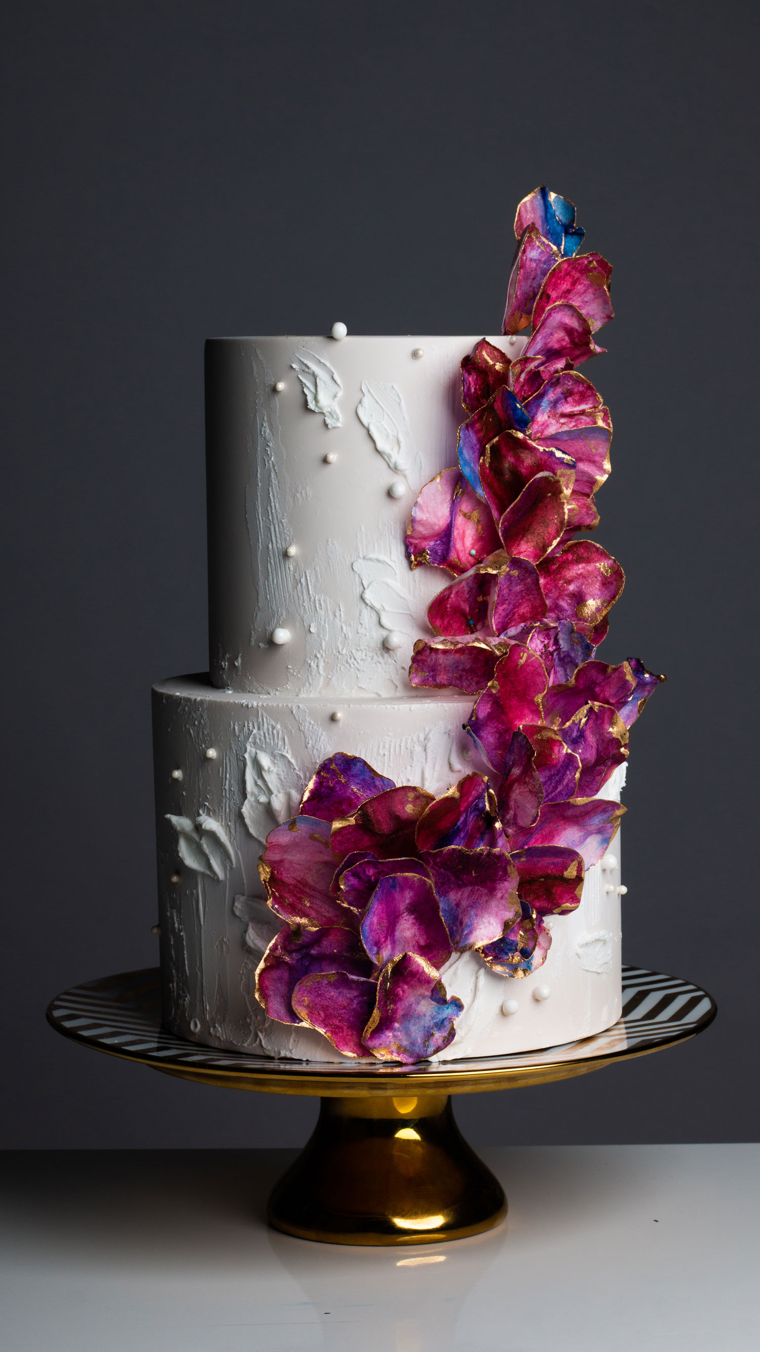 wafer parper wedding cake with pink and purple wedding flowers