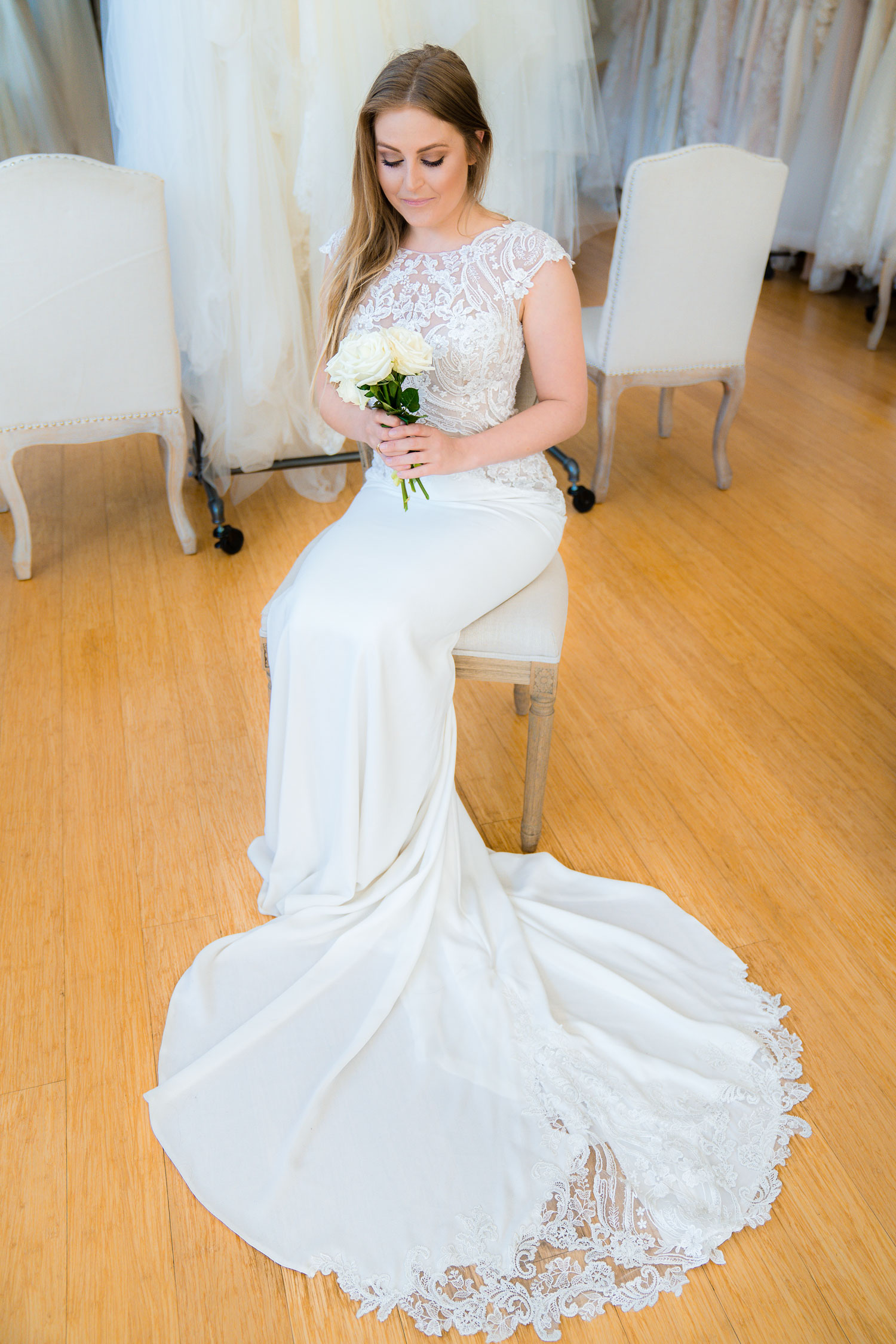 bride in pretty lace cap sleeve gown with bouquet sitting in chair trying on gown at the boutique by bbelle events