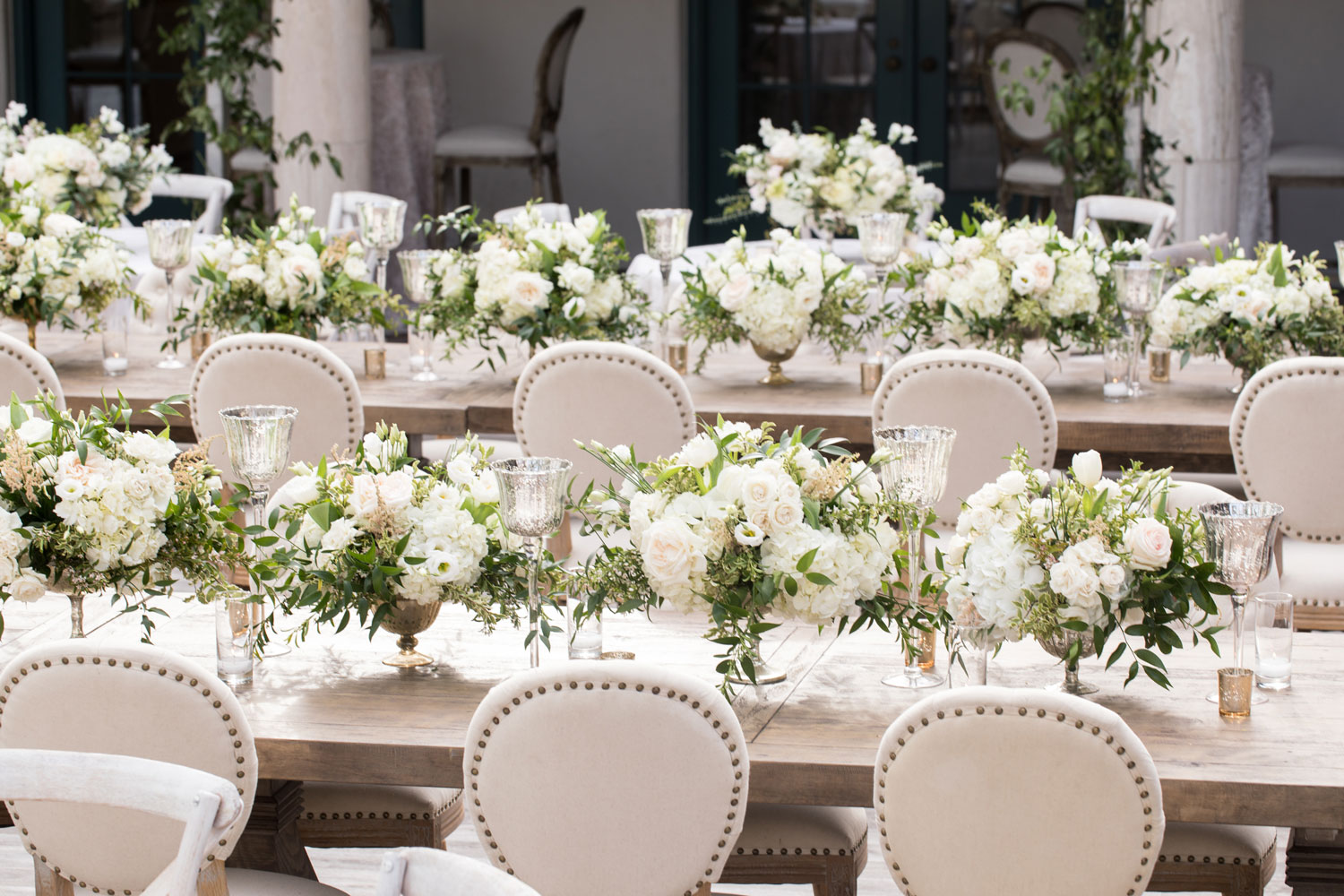long rustic chic king's table at wedding with low white centerpieces
