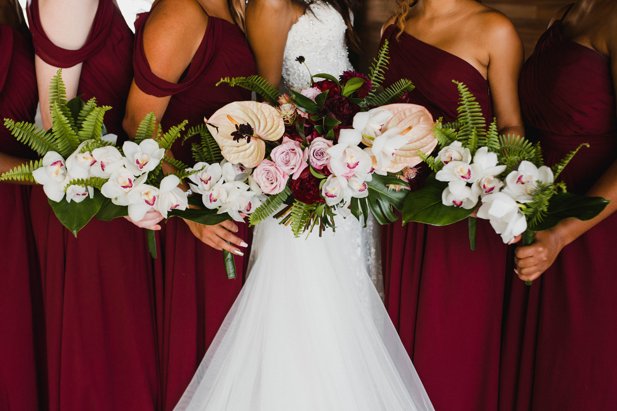 tropical bouquet bridesmaids in burgundy bridesmaid dresses white orchid bouquets
