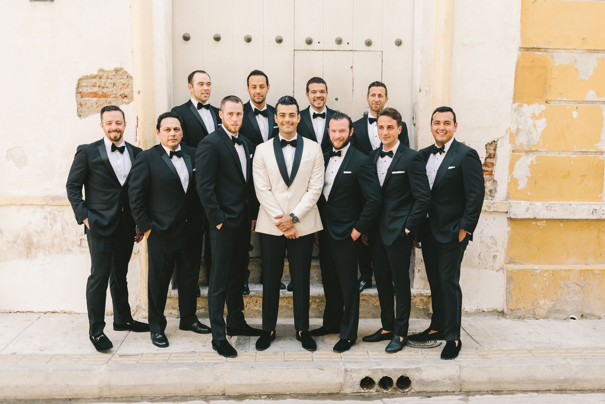 groom with off white jacket black lapels destination wedding with groomsmen groom style ideas
