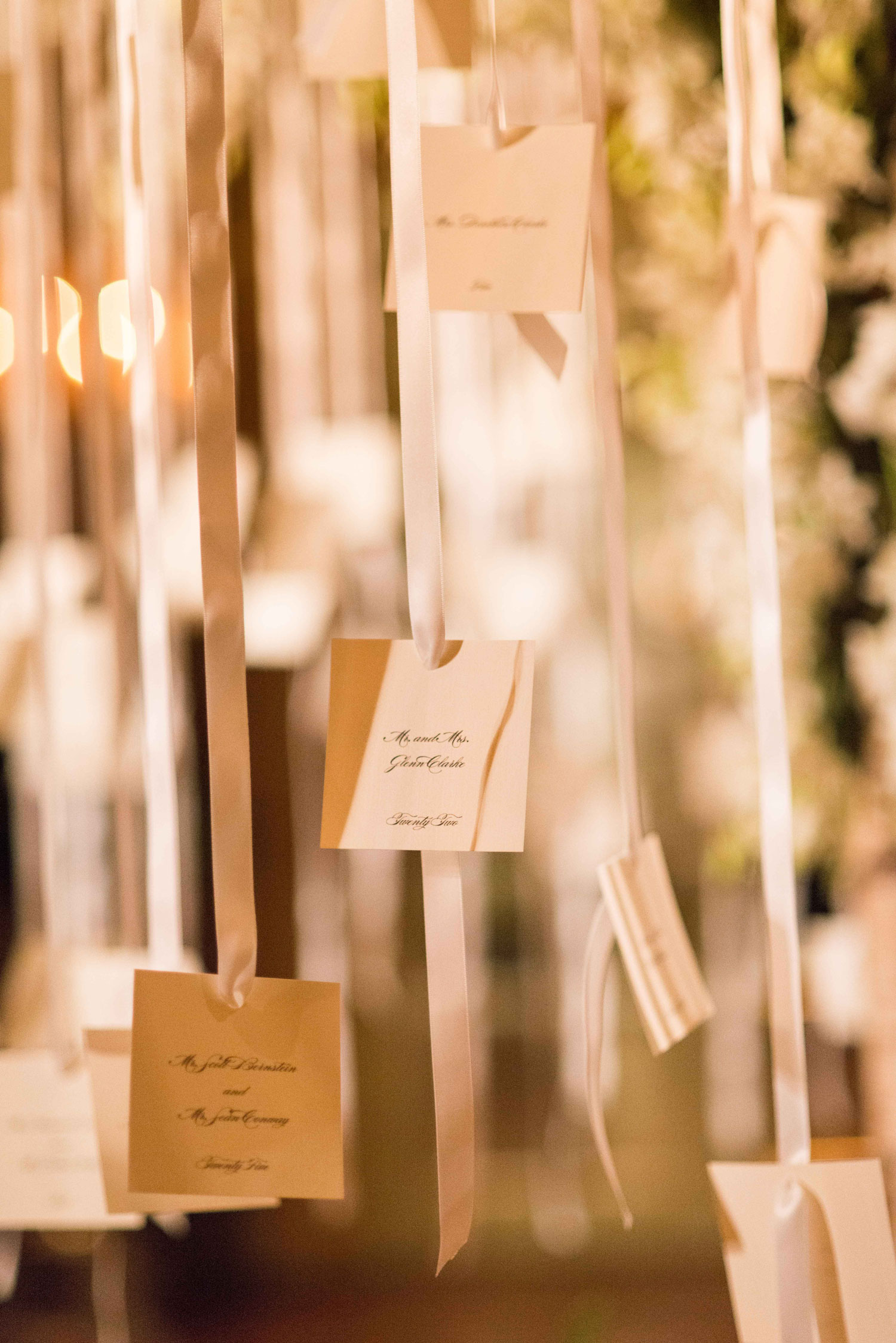 wedding escort cards attached to ribbon hanging from tree ceiling reception ideas