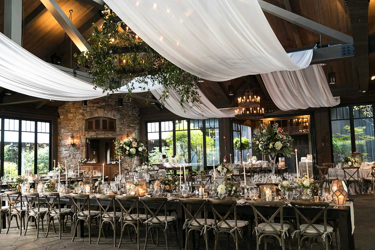 rustic elegant wedding reception with drapery hanging from wood beams over tables