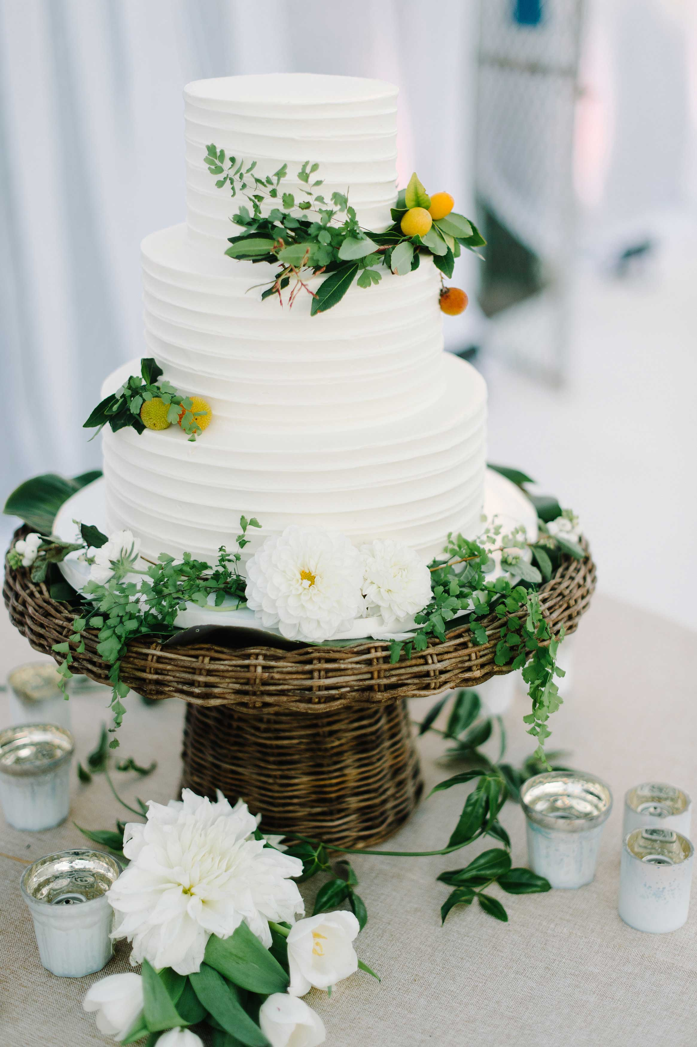 wedding cake white simple with fresh flowers and fruits on wicker stand