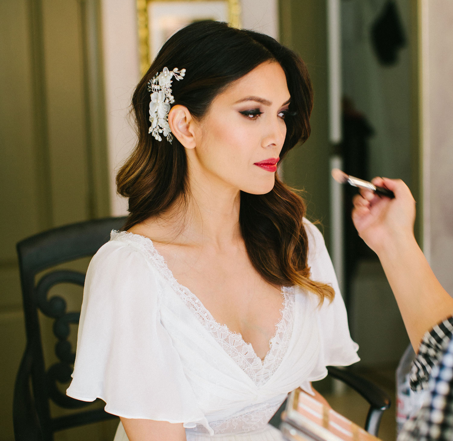 bride in white robe getting makeup done before wedding, how to make sure bridal makeup lasts throughout the day