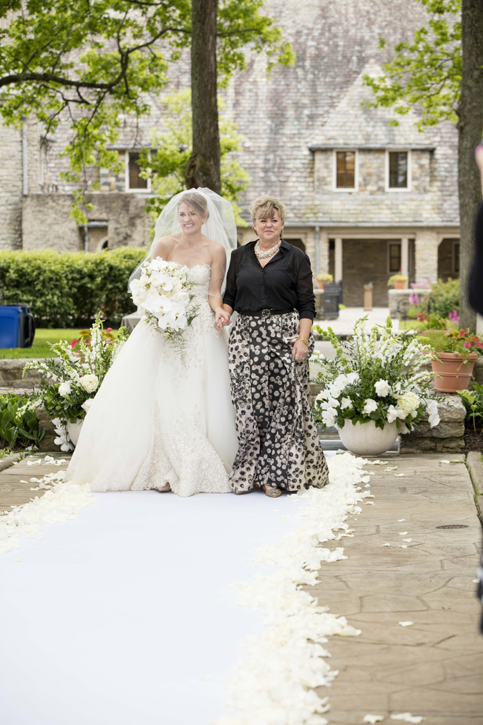 bride walking down aisle for outdoor wedding with mother of bride