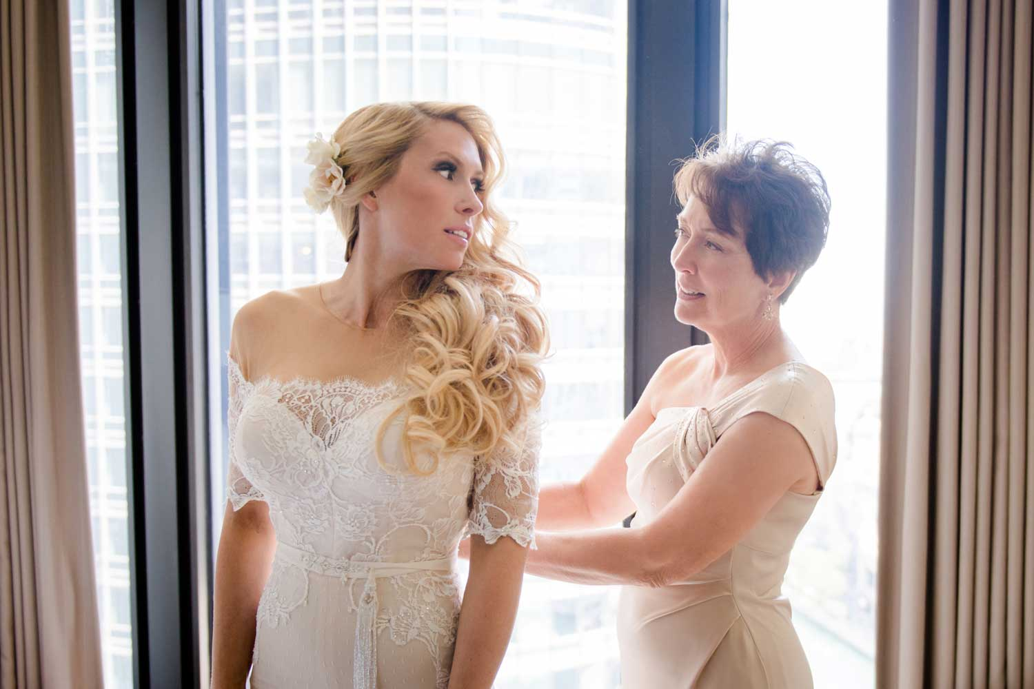 bride in illusion wedding dress getting ready with the help of her mother in a beautiful evening gown