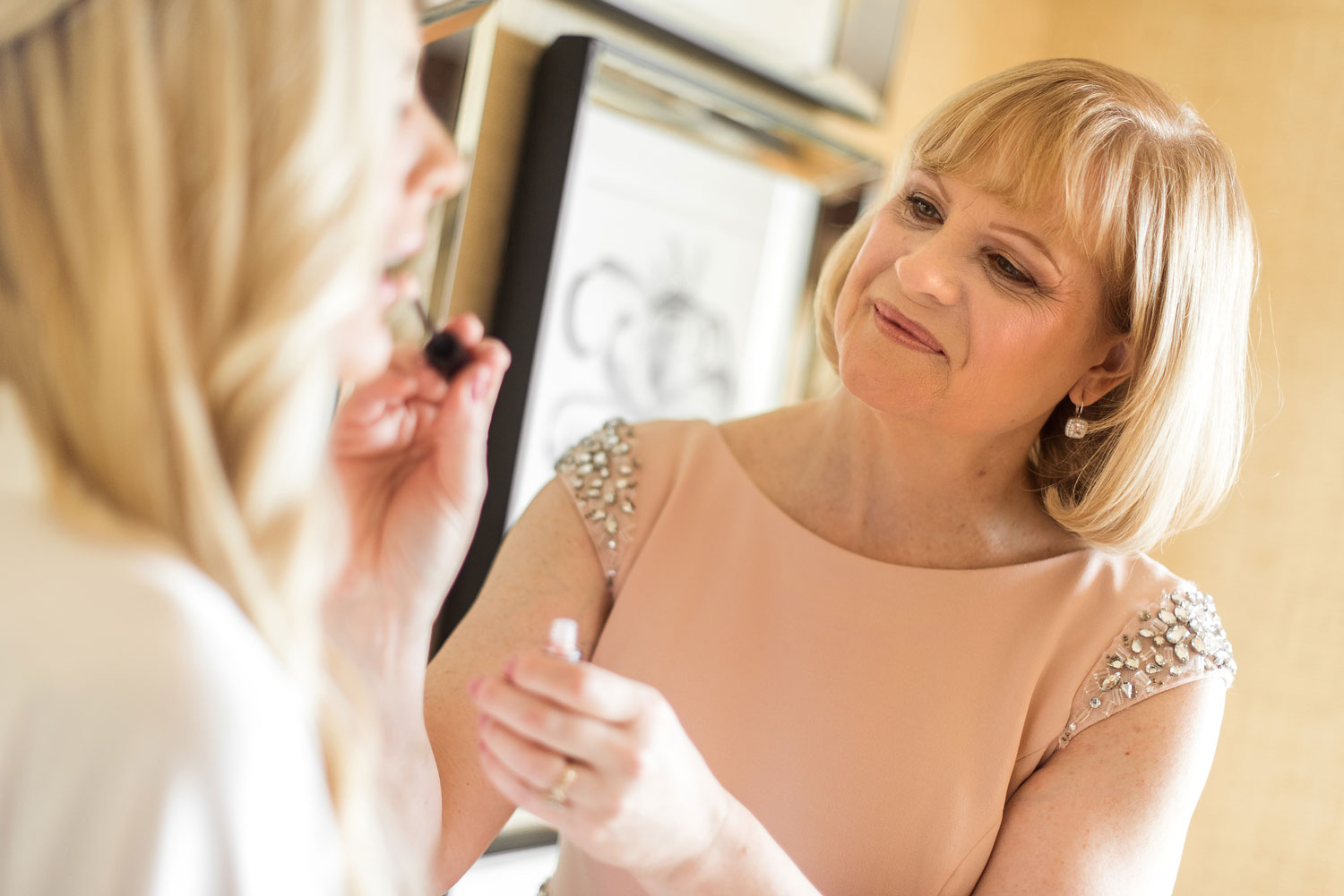 mother of the bride helping daughter with makeup while getting ready for wedding