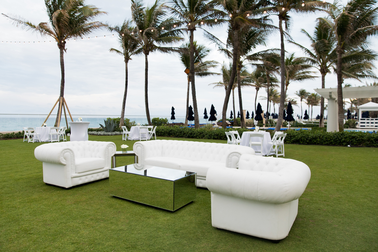 outdoor lounge area with white furniture at wedding cocktail hour palm trees in the background