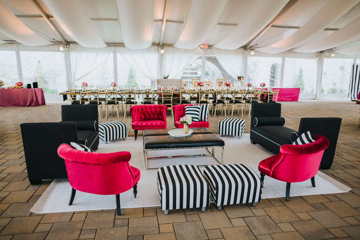 chic modern lounge area at wedding reception with black, hot pink, black and white striped furniture