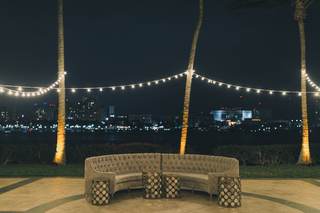 nighttime wedding reception outdoor lounge area with grey tufted furniture