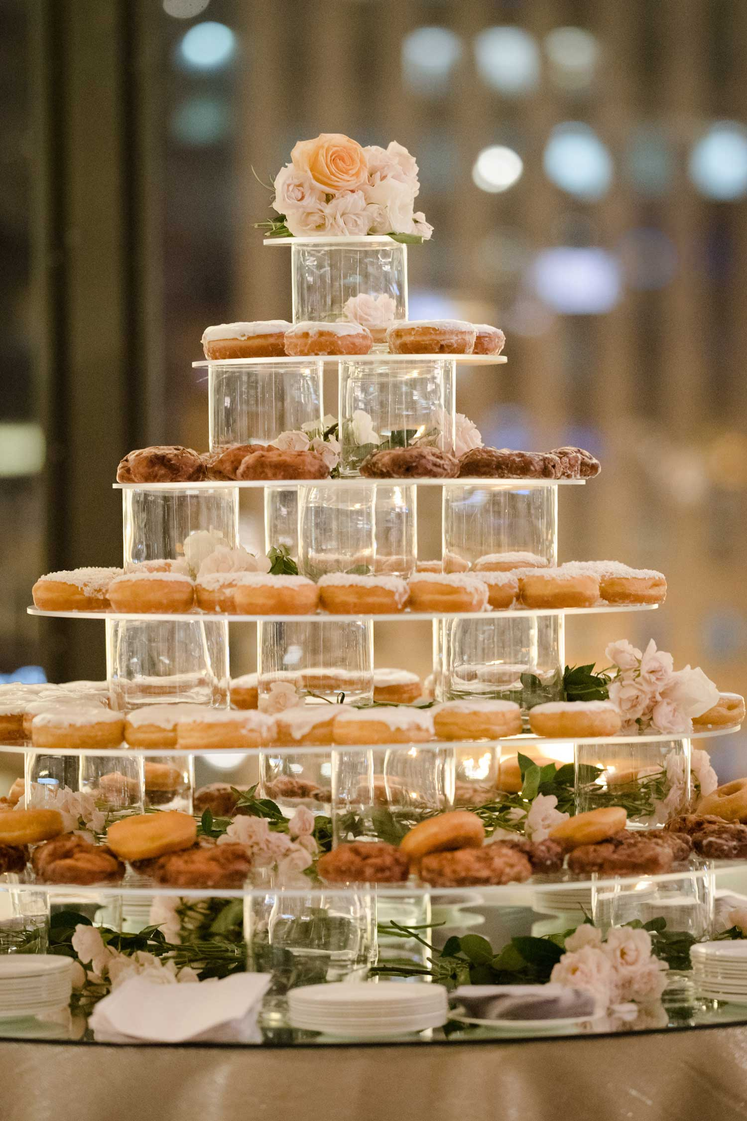Acrylic tower of donuts doughnuts at wedding reception dessert table