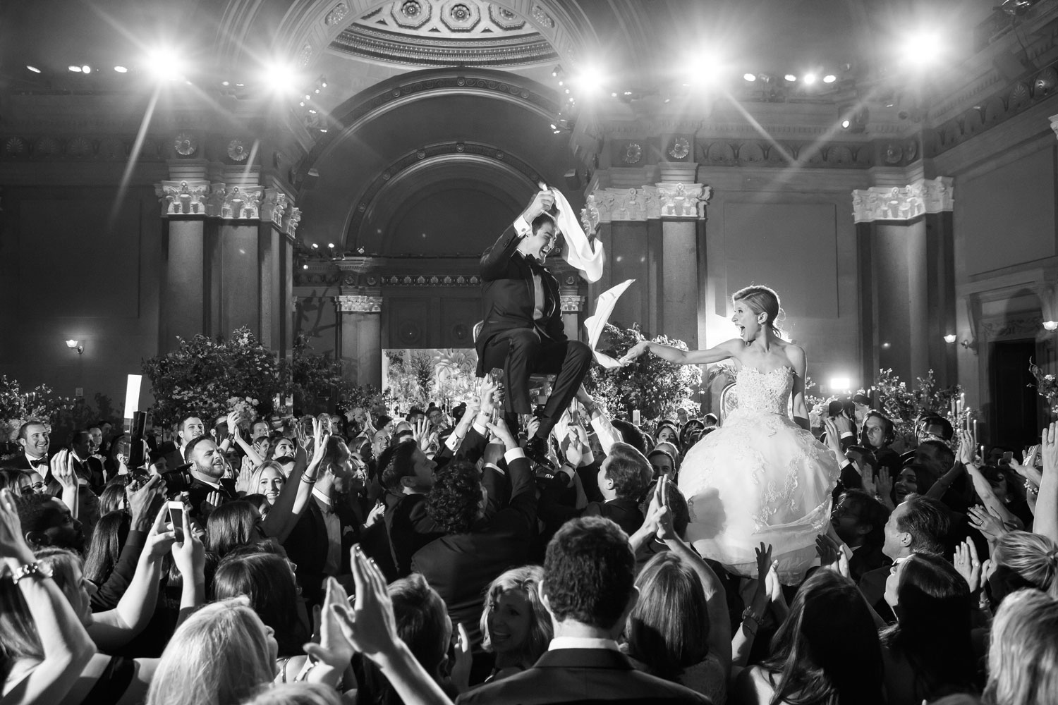 black and white photo of wedding reception guests lifting bride groom in air hora dance