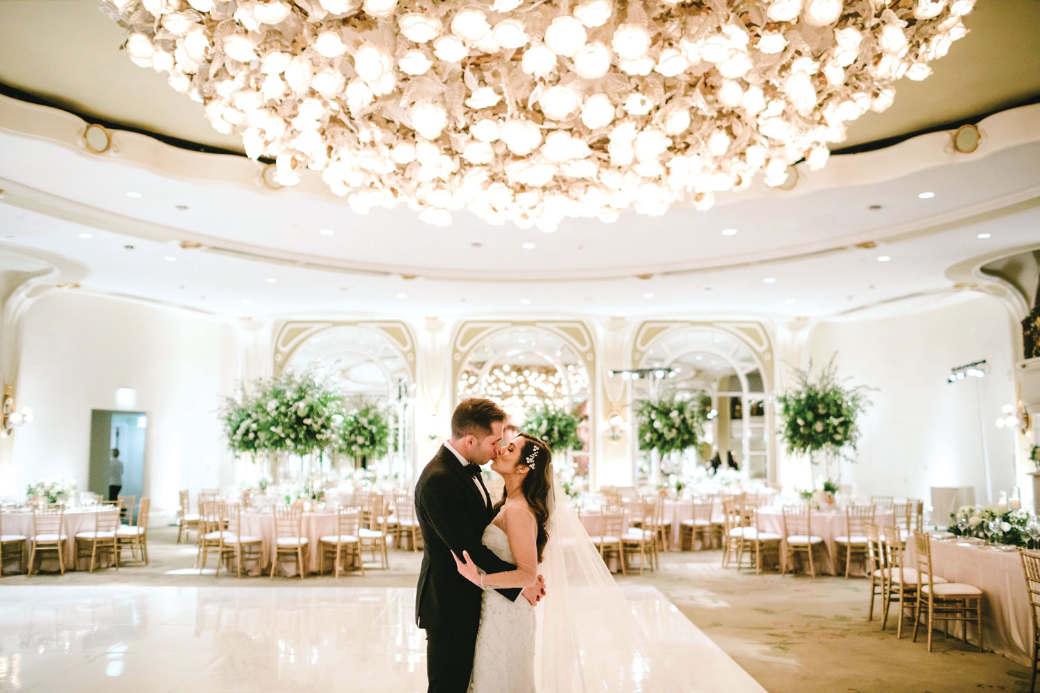 bride and groom kiss in empty ballroom wedding reception venue tessa lyn events planning tips