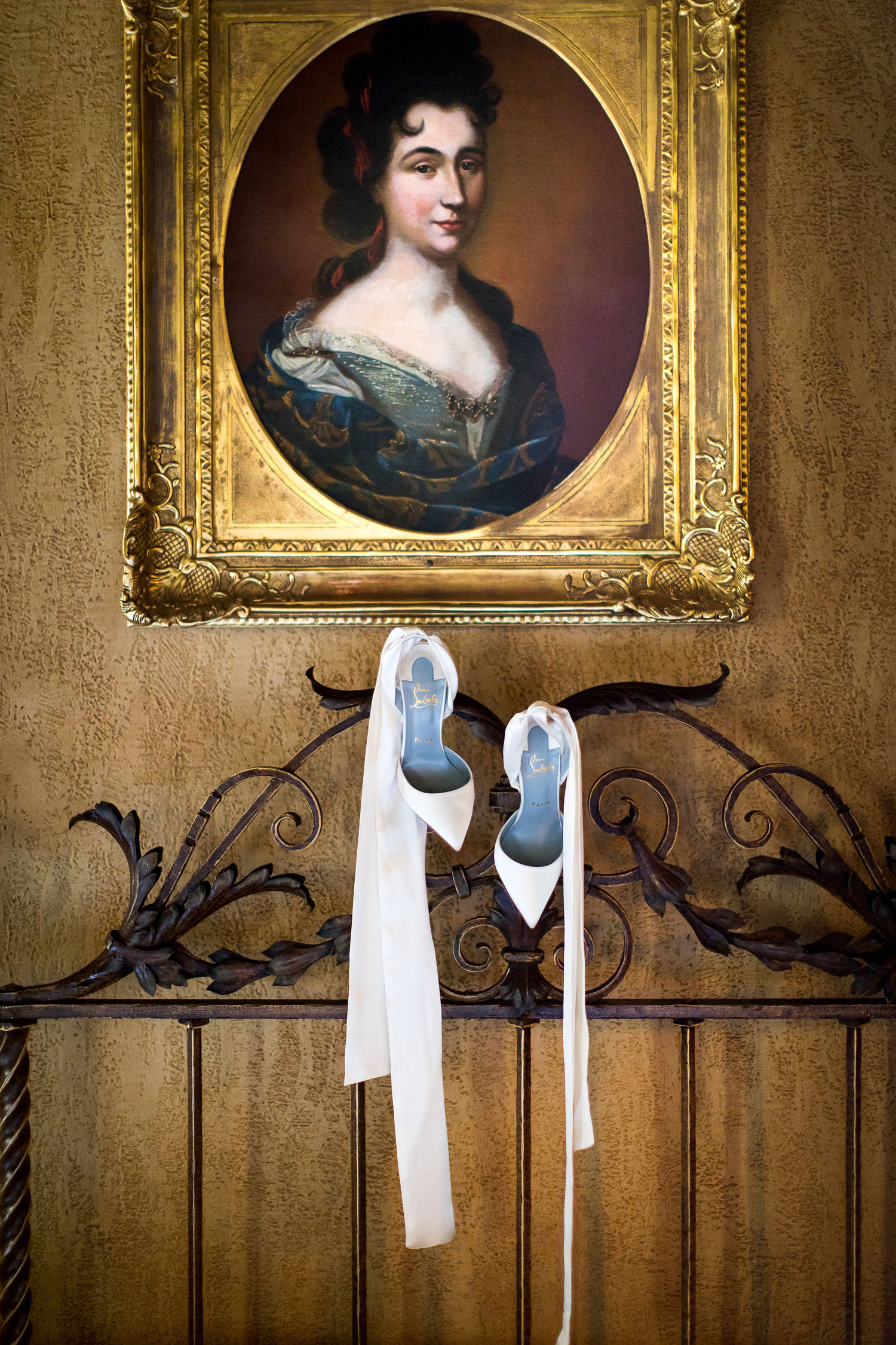 luxury wedding shoes hanging with portrait artwork white satin pumps christian louboutin ribbon ankle straps