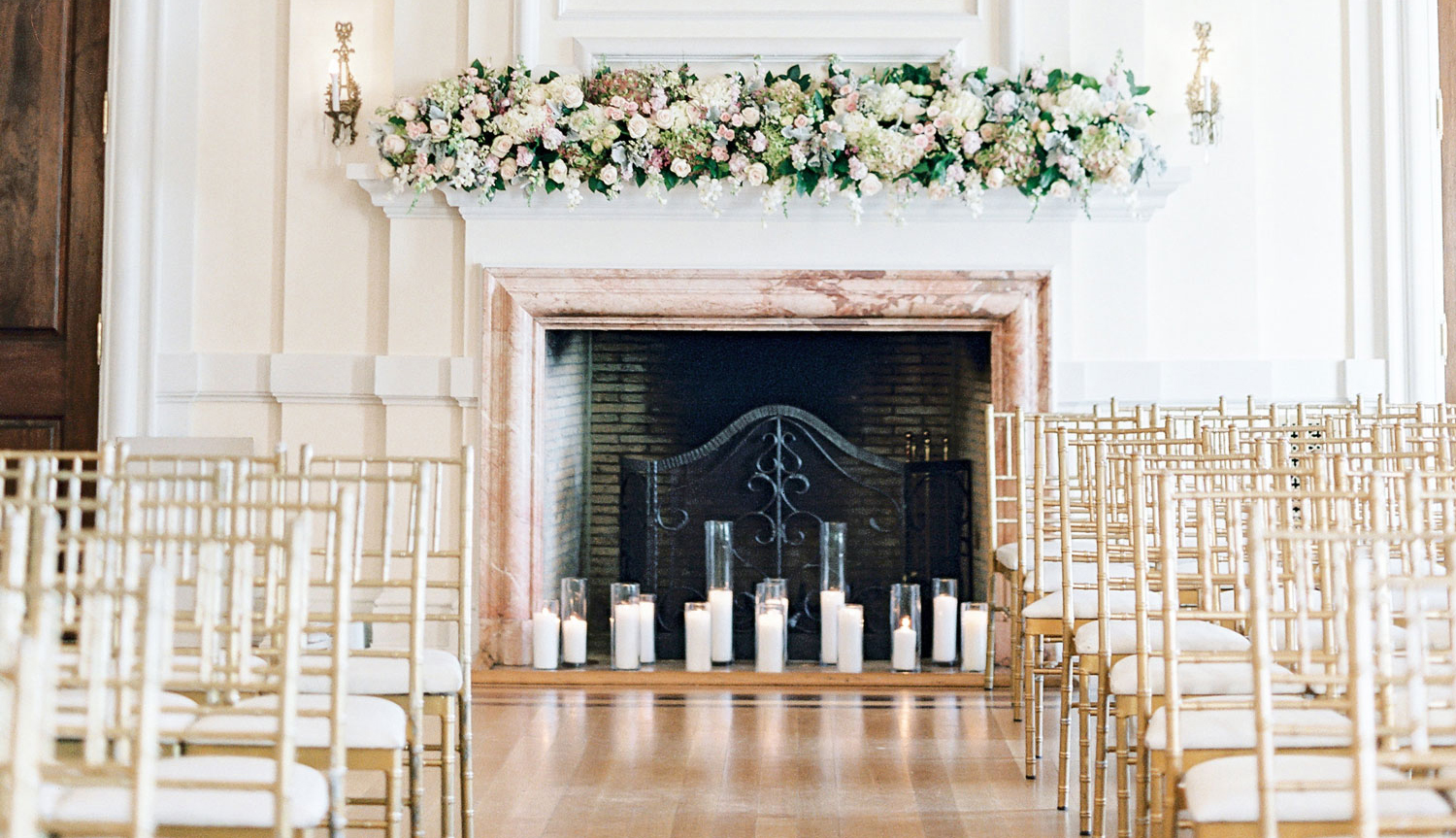indoor wedding set up in front of fireplace with candles, gold chiavari chairs setup for pop-up wedding