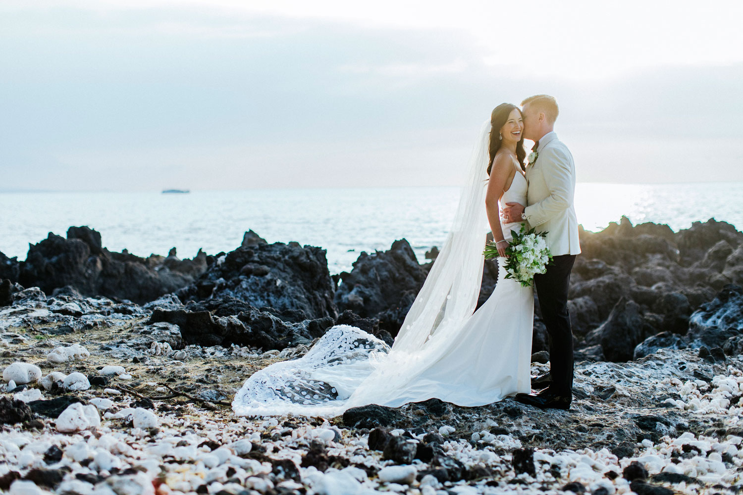 photo of couple on ocean rocks in hawaii, what does your wedding season say about your personality?