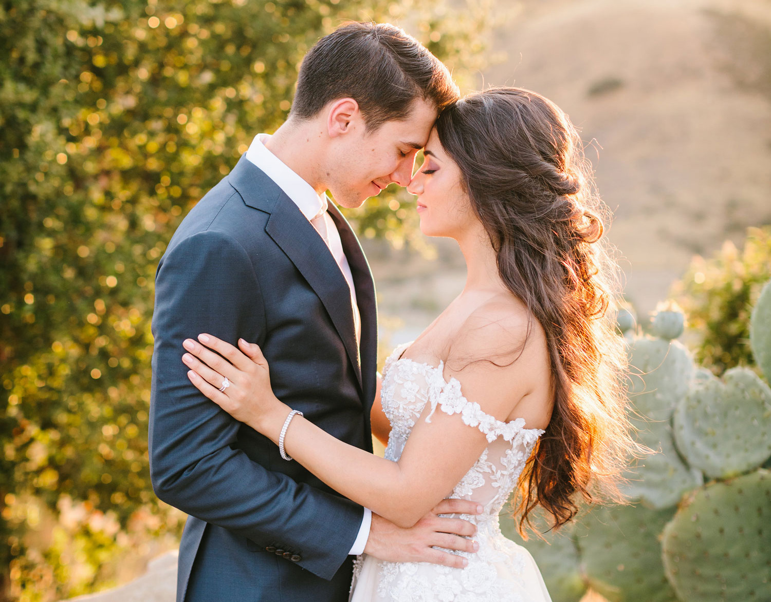 photo of groom in navy suit and bride in lace off-the-shoulder dress holding each other while foreheads touch