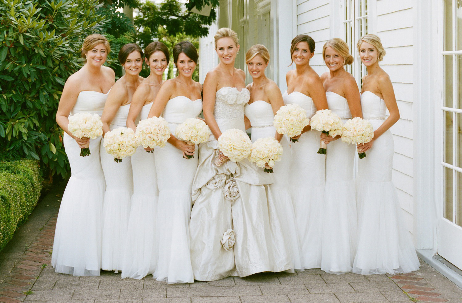 bride in ornate wedding dress with rose pickups in the middle of bridesmaids in strapless white dresses