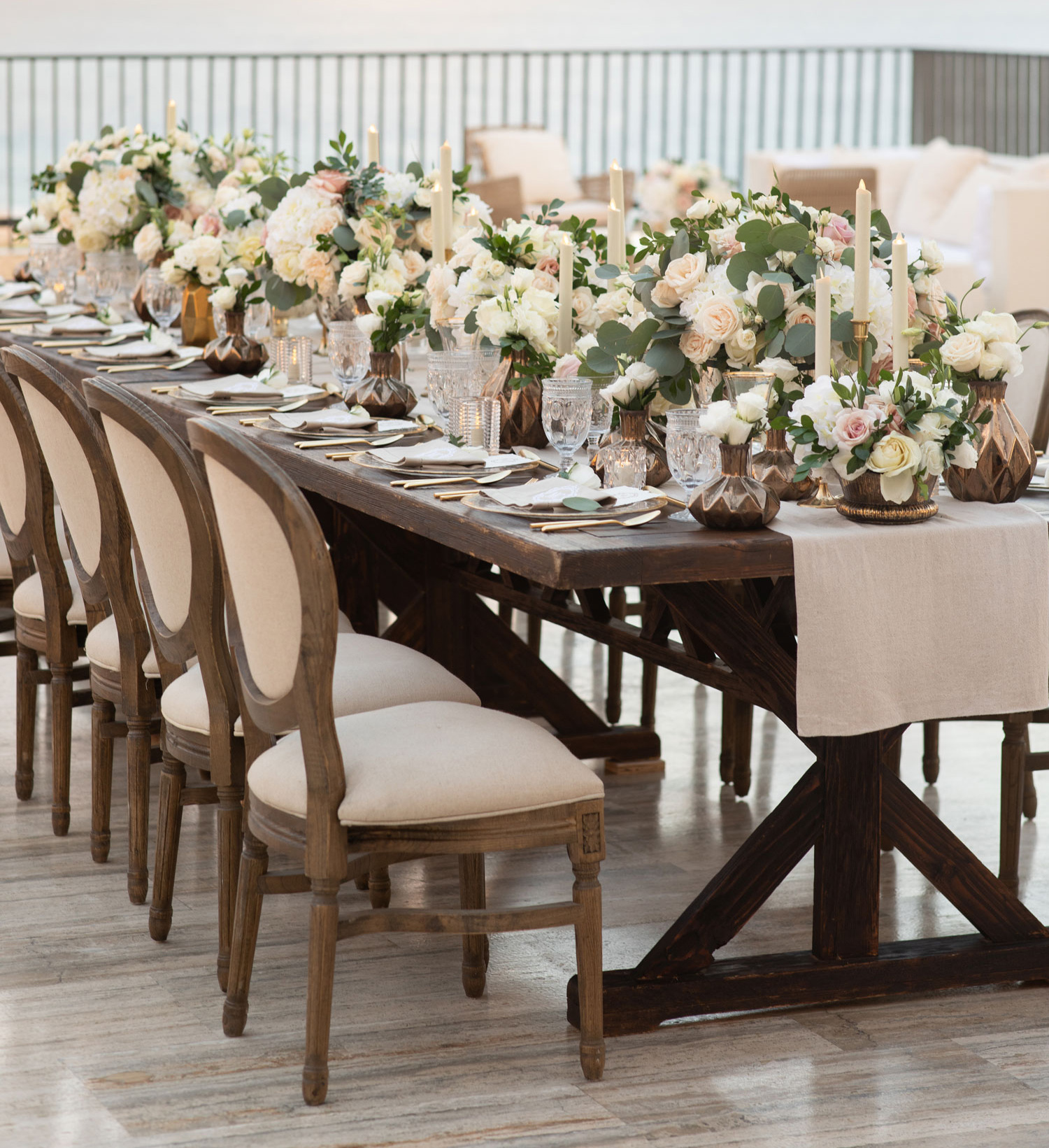 outdoor wedding reception on balcony with wooden & fabric chairs, fake candles and eucalyptus