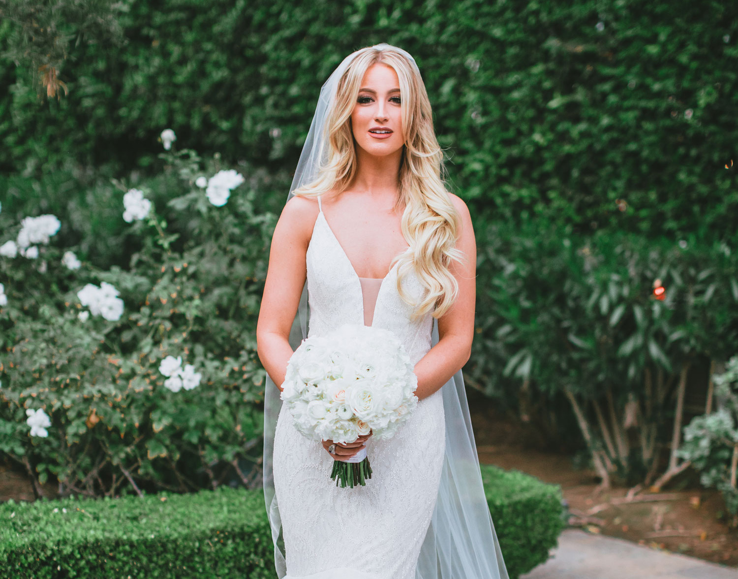 bride with long blonde hair in beaded wedding dress with spaghetti straps and plunging illusion neckline
