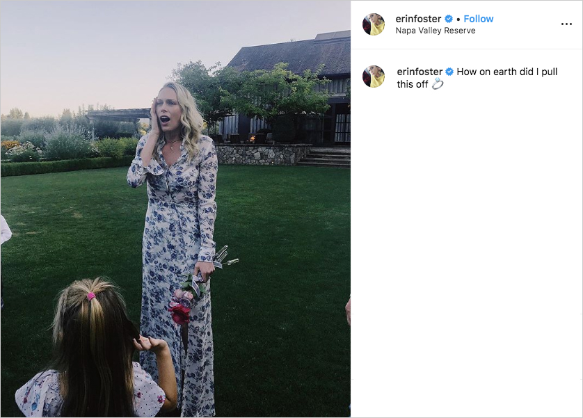 erin foster reacting to her engagement in disbelief, with jaw dropped, holding small bouquet of red, pink, and lavender roses