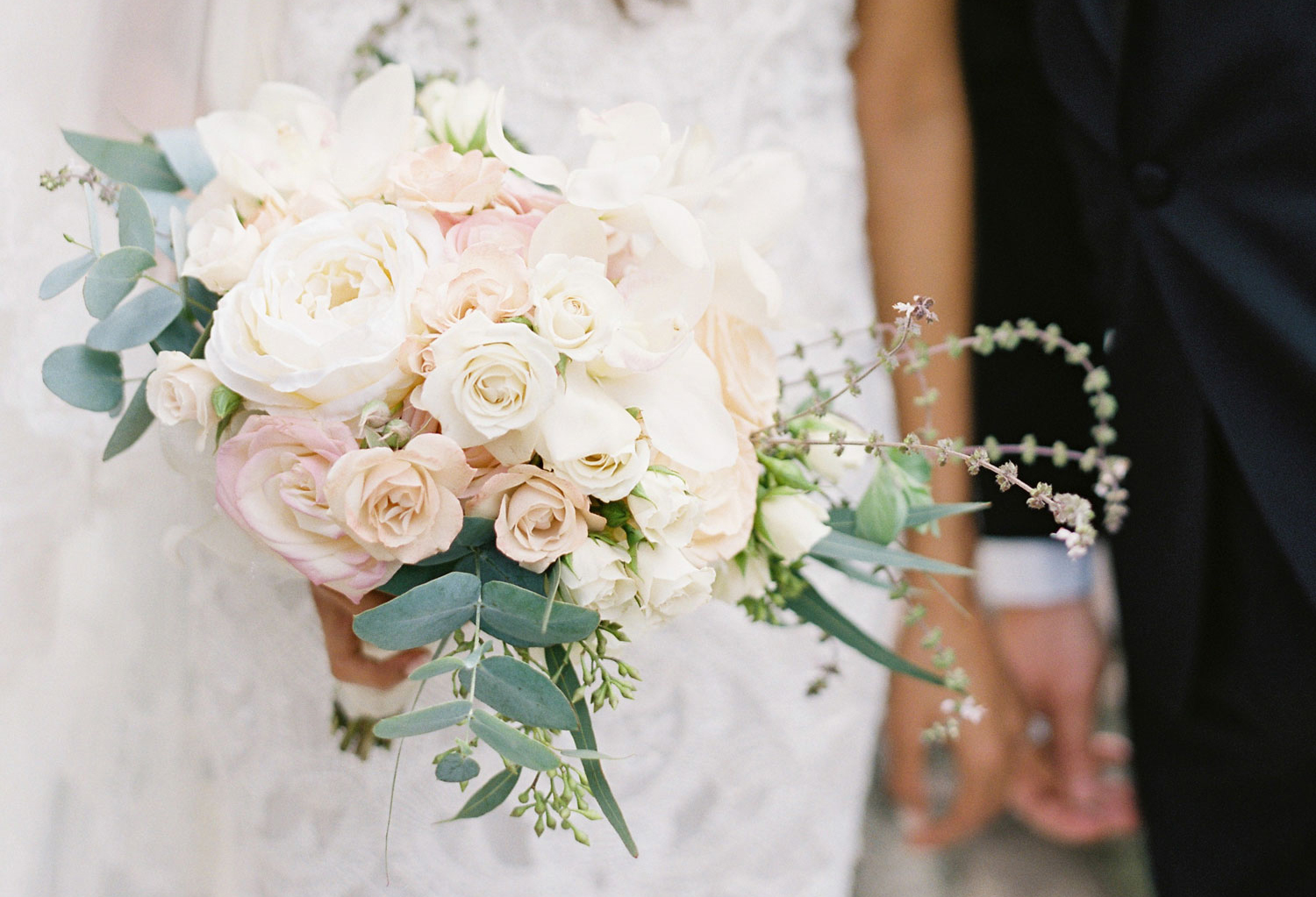 soft bridal bouquet with white and blush-tinged roses and eucalyptus leaves