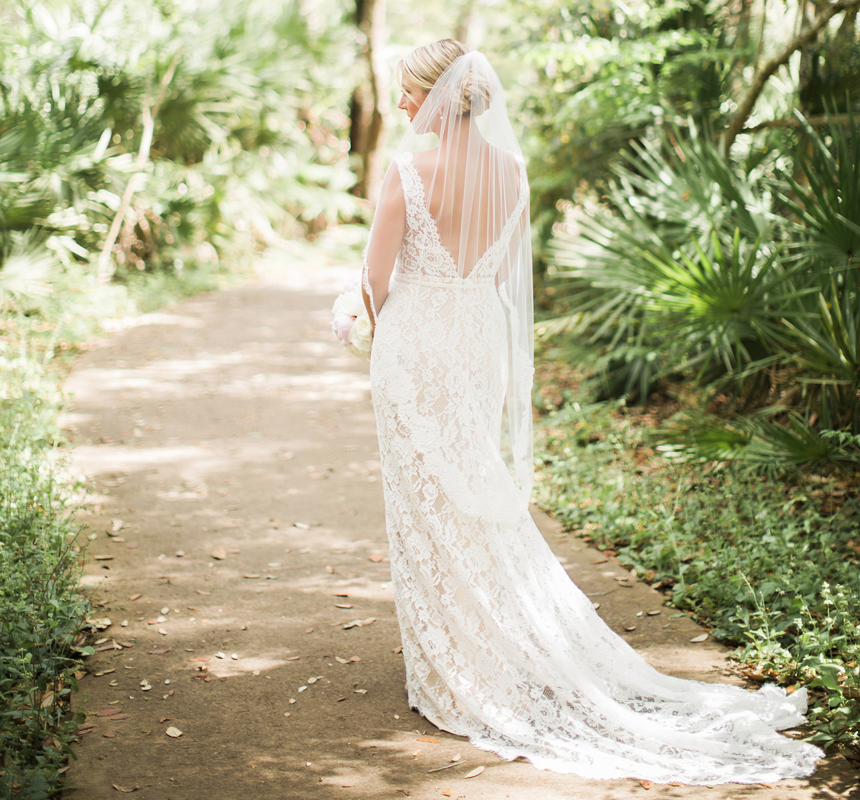 back view of bride in lace gown with deep v back and veil on path in the woods