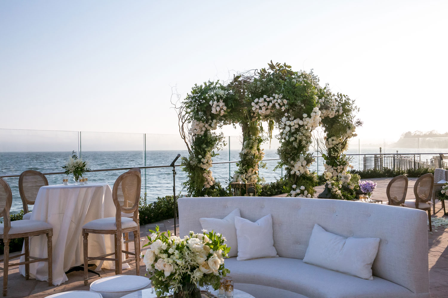 rooftop wedding with lounge area on one side and chuppah made with lush greenery on the other