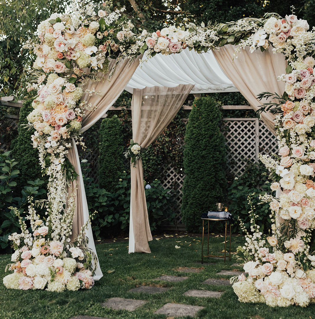 chuppah made with white and taupe drapery and lush floral arrangements with ivory flowers and greenery