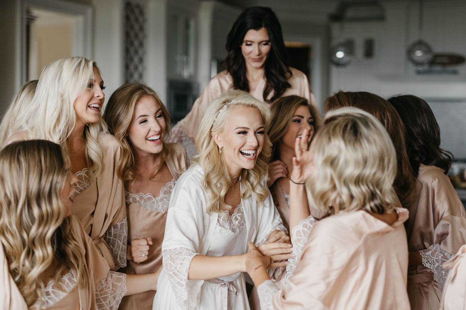 bride with bridesmaids in getting ready robes laughing together the morning of the wedding