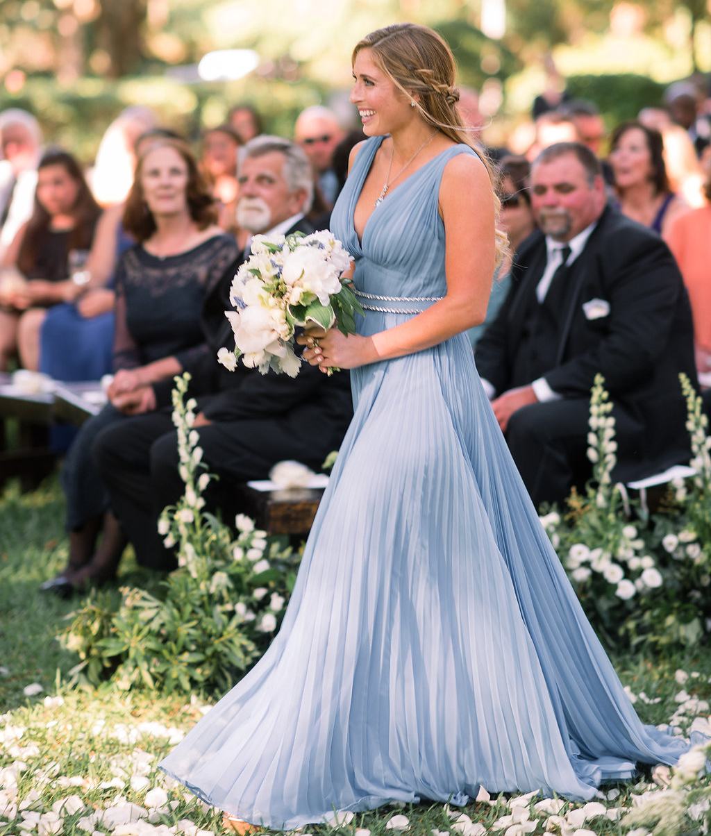 blonde maid of honor in pleated sky blue dress holding bouquet while walking down the aisle