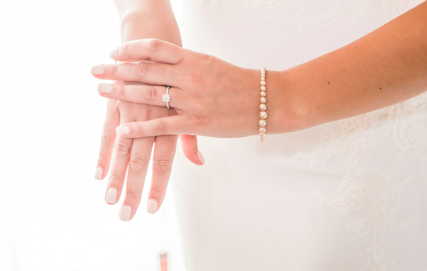 woman's hands with ivory manicure, one hand on top with pearl bracelet and round diamond engagement ring with pavé band