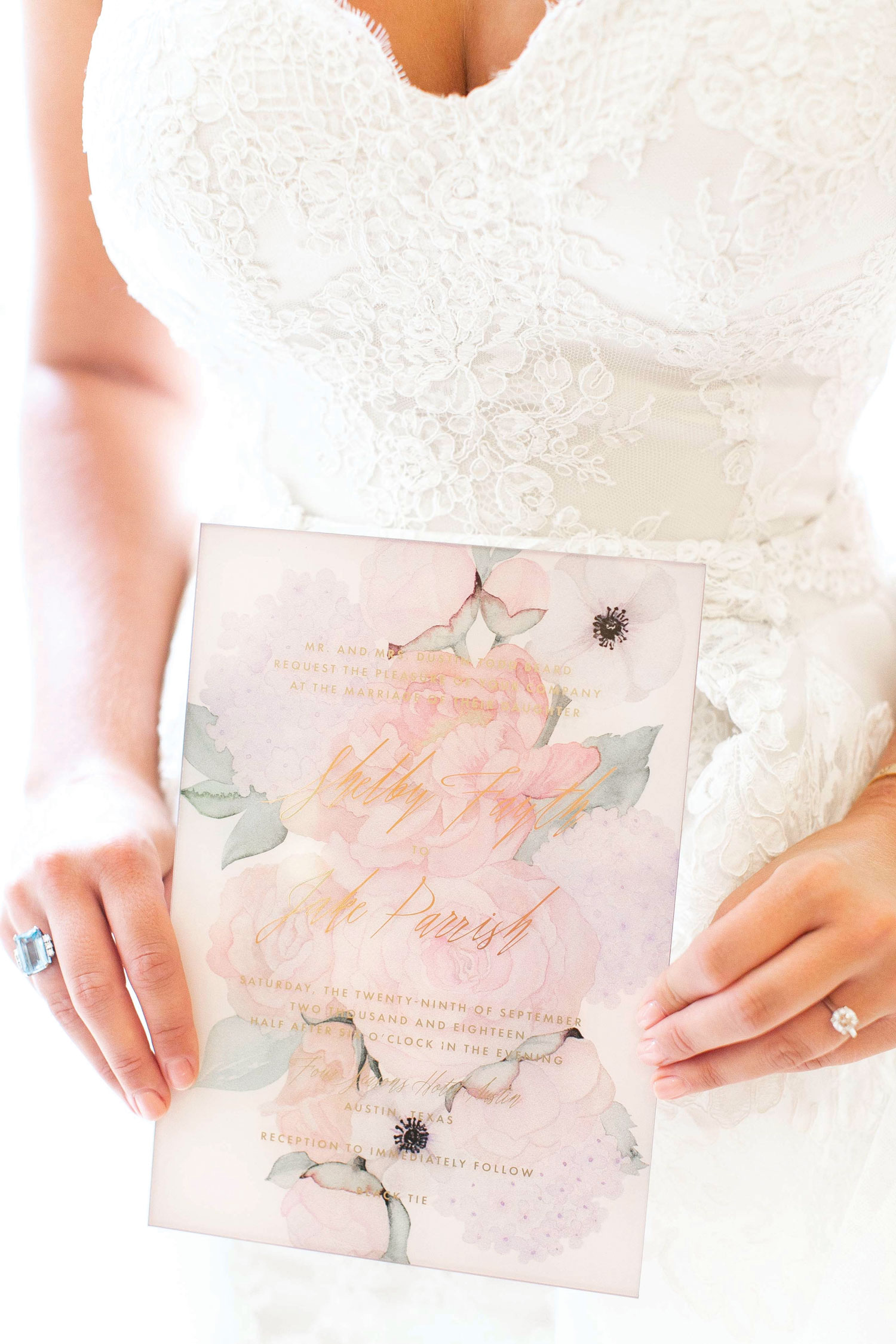 bride holding pretty flower print wedding invitation with watercolor floral design
