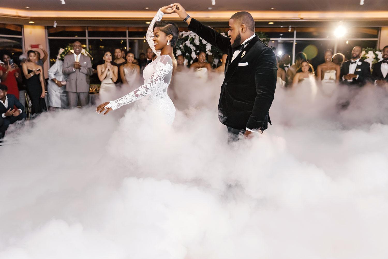bride and groom first dance at wedding reception luxury ballroom smoke fog on dance floor