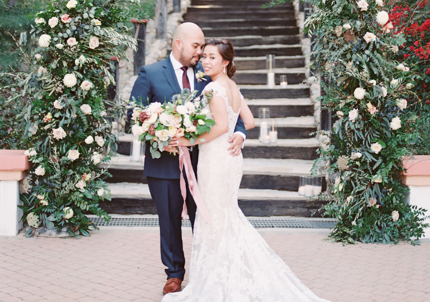 bride and groom in front of wooden staircase with florals and greenery on both sides